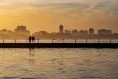 Silhouettes of two figures on Montrose Breakwater in Chicago during a hazy sunset. Fall 2020.